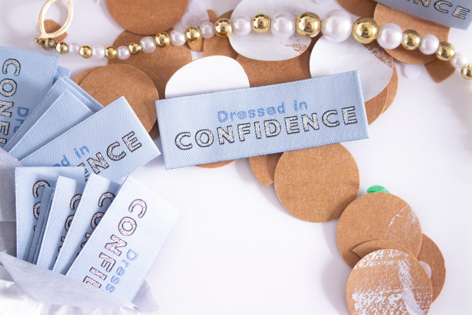 Light blue woven labels that reads Dressed in Confidence made by Au Atelier